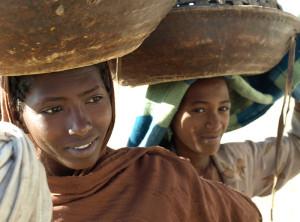 Zwei Mädchen Kalebassen tragend